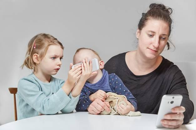 Der Griff zum Smartphone ist für Kinder und Eltern oft verlockend. Definierte Handy-Zeiträume können dagegen schützen.
