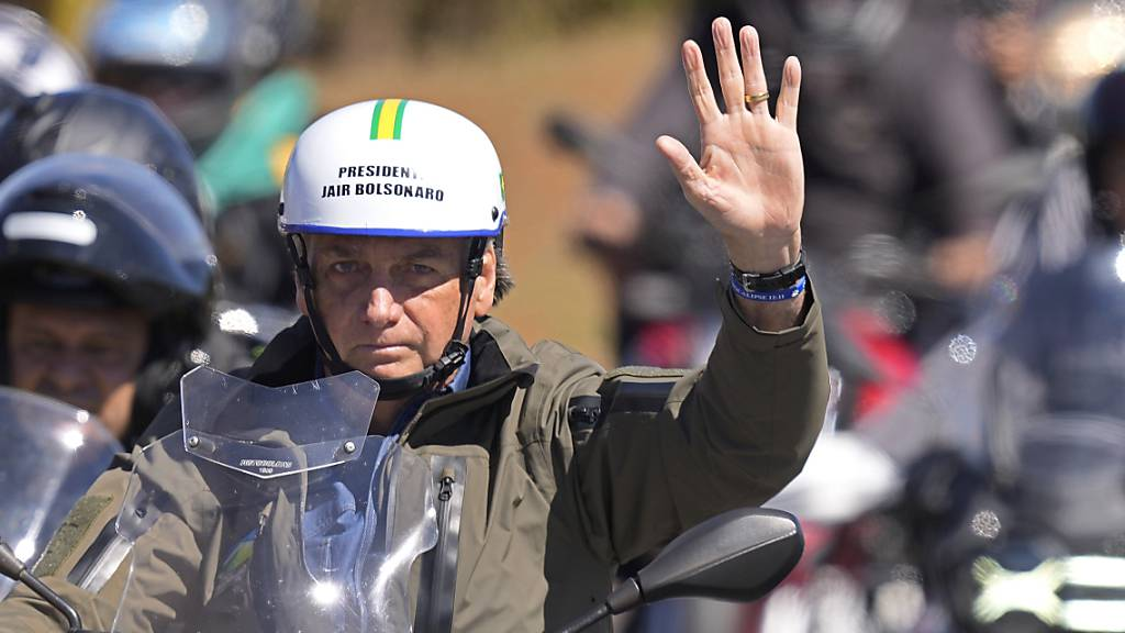 Jair Bolsoanro, Präsident von Brasilien, trägt während einer Motorrad-Rallye anlässlich des Vatertags in Brasilien, einen Helm mit seinen Initialen. Foto: Eraldo Peres/AP/dpa