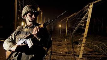 Ein indischer Soldat hält in der Nähe der nordindischen Stadt Jammu an der Grenze zu Pakistan Wache