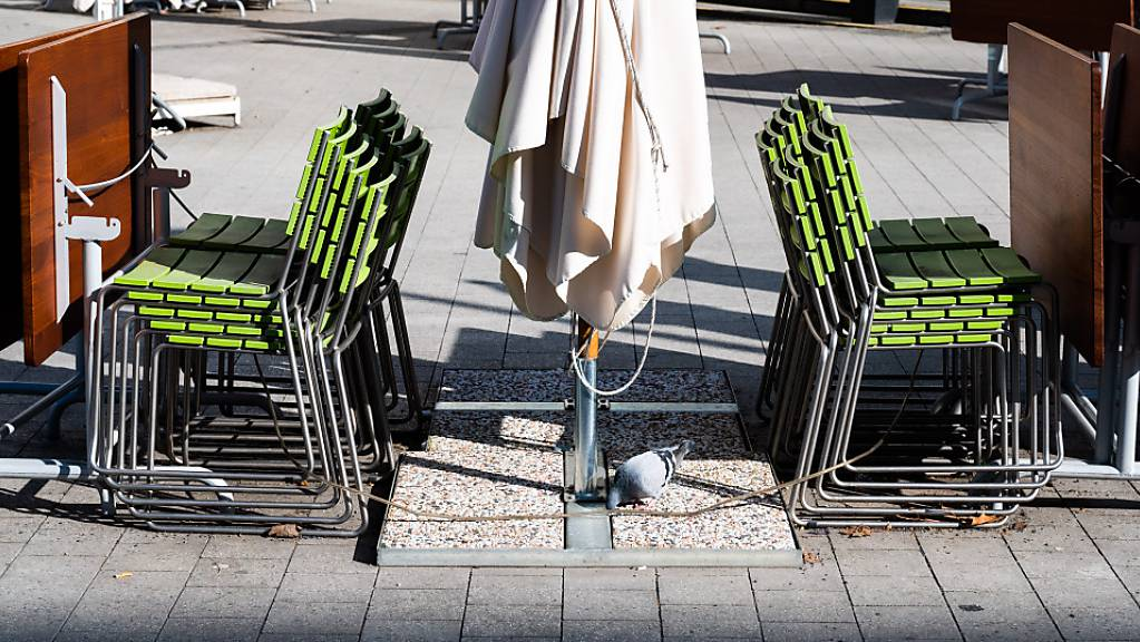 Gestapelte Stühle und zusammengeklappte Tische stehen in der Außengastronomie eines geschlossenen Restaurants in der Hannoveraner Innenstadt.