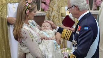 König Carl Gustaf von Schweden und Prinzessin Madeleine betrachten den Täufling Adrienne, Carl Gustafs siebtes Enkelkind. Die Kleine verschlief den grössten Teil der Zeremonie.