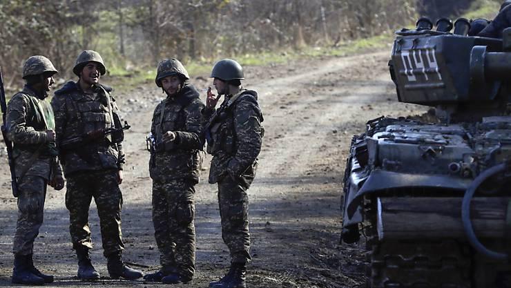 Ethnisch armenische Soldaten stehen an einem Kontrollpunkt auf einer Straße nach Schuscha in der Südkaukasusregion Berg-Karabach. Russland hat gemäß einer Vereinbarung mit den beiden Konfliktparteien Armenien und Aserbaidschan mit der Entsendung von Friedenstruppen in das Gebiet begonnen. Foto: Sergei Grits/AP/dpa