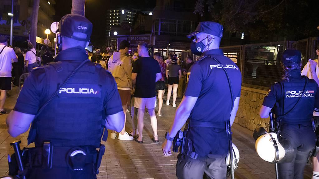 ARCHIV - Die Polizei fordert Menschen, die am Strand von Arenal trinken, zum Gehen auf. Foto: Clara Margais/dpa