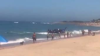 Ein überfülltes Flüchtlingsboot kommt am Strand in Spanien an – während sich Badegäste sonnen.