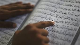 Ein Mann liest im Koran (Symbolbild)