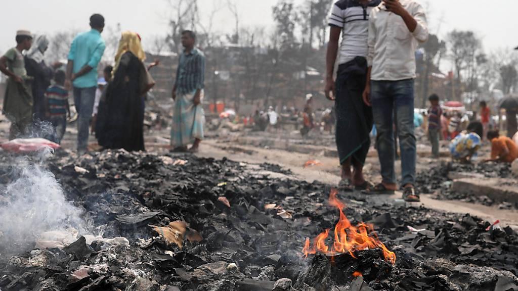 Rohingya-Flüchtlinge stehen im Rohingya-Flüchtlingslager Balukhali und suchen in der Asche nach Brauchbarem. Foto: Kazi Salahuddin/ZUMA Wire/dpa