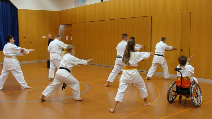 Mit grossem Fokus führen die Teilnehmenden im Karatetraining ihre Bewegungen aus.