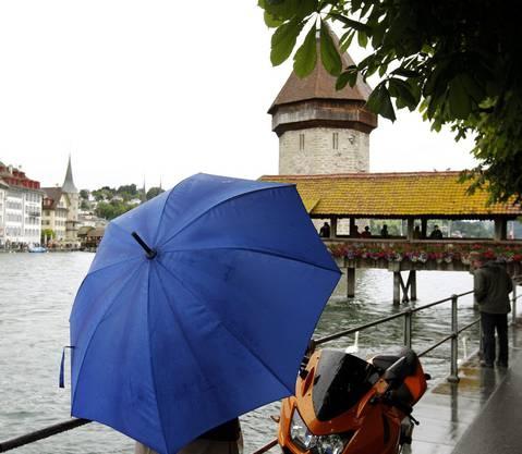 Eine Gruppe Touristen geniesst die Stadt Luzern trotz viel Regenschauer und Wolken am Dienstag 12. Juni 2012 in der Altstadt von Luzern.