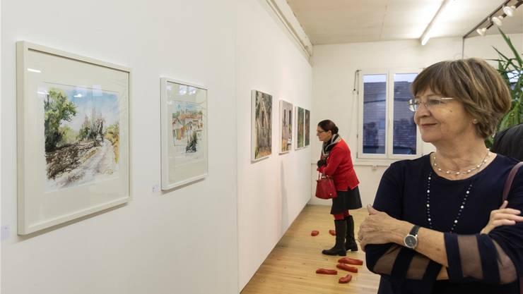 Besucherinnen der Vernissage lassen die Kunst auf sich einwirken. Die roten Fussabdrücke am Boden stellen irreale Besucher dar.