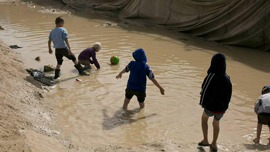 ARCHIV - Kinder spielen in einer Schlammpfütze in der Abteilung für ausländische Familien im Lager Al-Hol in der Provinz Hasakeh. Foto: Maya Alleruzzo/AP/dpa