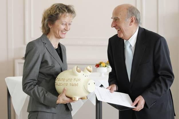 Der damalige Bundesrat Hans-Rudolf  Merz übergibt Widmer-Schlumpf bei der Schlüsseluebergabe des Finanzdepartements ein Sparschwein und die Traktanden der nächsten Bundesratssitzung.