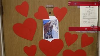 """ARCHIV - Herzen, ein Foto und ein Polizeisiegel kleben an der Tür zur Wohnung der 85-jährigen Holocaust-Überlebenden Mireille Knoll, in der sie am Freitag tot aufgefunden worden ist. (zu dpa """"Mordprozess im Fall der in Paris getöteten Jüdin Knoll angeordnet"""" am 13.07.2020) Foto: Christophe Ena/AP/dpa"""