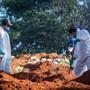 dpatopbilder - Friedhofsmitarbeiter in Schutzanzügen schaufeln Erde auf dem Friedhof Vila Formosa in der brasilianischen Stadt Sao Paulo inmitten der Corona-Pandemie. Foto: Lincon Zarbietti/dpa