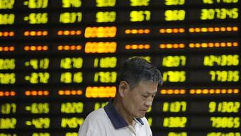 Ein Chinese steht niedergeschlagen vor einer Digitalanzeige mit Börsendaten - die chinesische Regierung will nach dem Taucher der Börse mit Stützkäufen eingreifen. (Symbolbild)