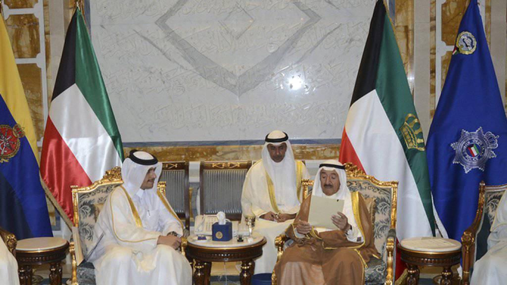 Kuwaits Emirs Scheich Sabah (rechts) liest ein Schreiben, das ihm der Aussenminister Katars, Mohammed bin Abdulrahman Al Thani (links) überreicht hat.