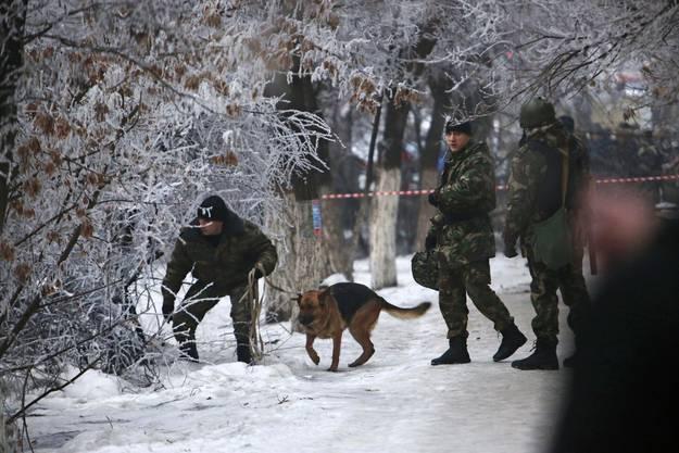 Polizisten suchen die Umgebung mit Spürhunden ab.