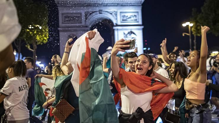 Ausgelassener Jubel: Algerische Fussballfans feiern vor dem Arc de Triomphe in Paris
