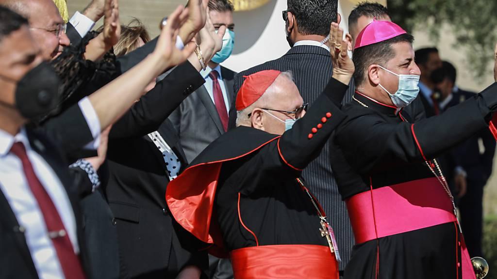 Barham Saleh (2.v.l), Präsident des Irak, und hochrangige Vertreter der katholischen Kirche winken Papst Franziskus während seiner Abflugzeremonie auf dem Internationalen Flughafen zu. Foto: Ameer Al Mohammedaw/dpa