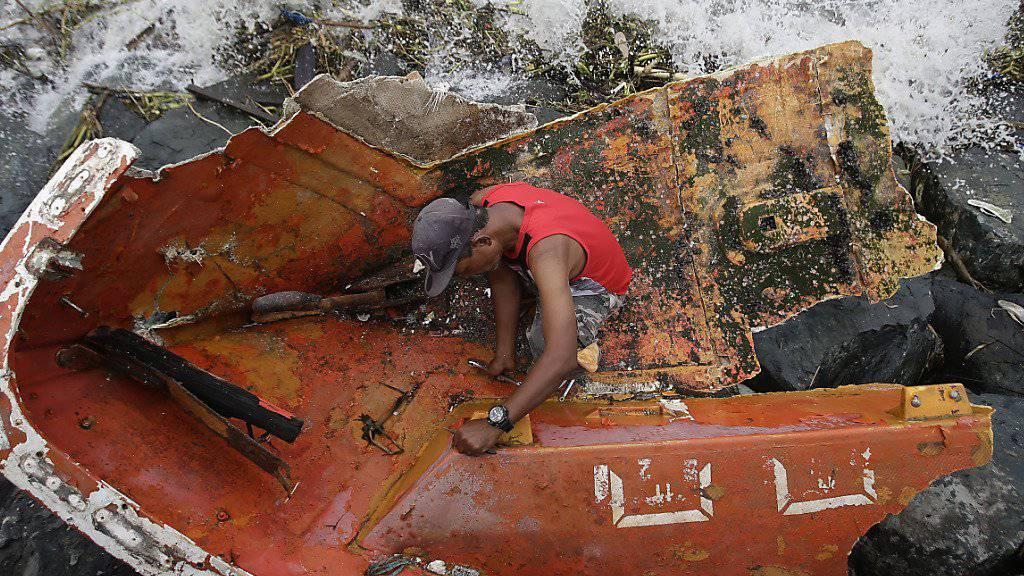 Ein Mann sammelt das Metall eines zerstörten Bootes, das der Taifun Haima bei Manila an Land schwemmte.
