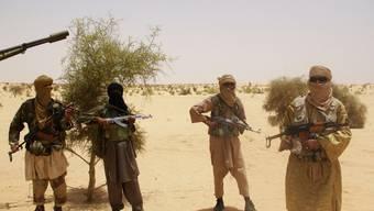 Bewaffnete Männer der islamistischen Organisation Ansar Dine bereiten die Übergabe vor