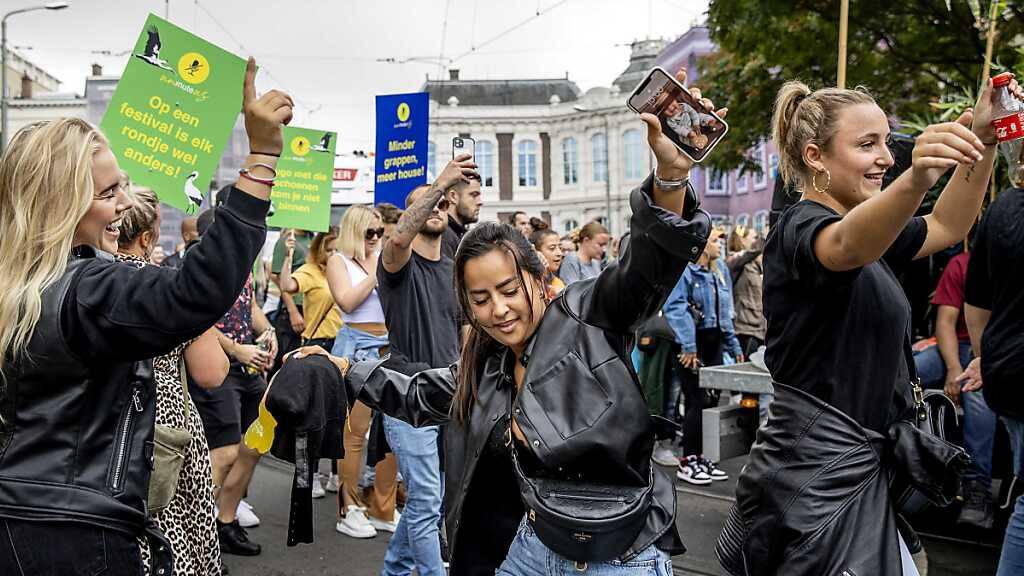 Teilnehmer eines Protestmarsches unter dem Motto «Unmute Us» ziehen durch die Stadt. Gemeinsam mit Djs, Musikern und Festivalorganisatoren haben in zehn niederländischen Städten Zehntausende Demonstranten die Aufhebung der Corona-Beschränkungen für die Veranstaltungsbranche gefordert. Foto: Koen Van Weel/ANP/dpa