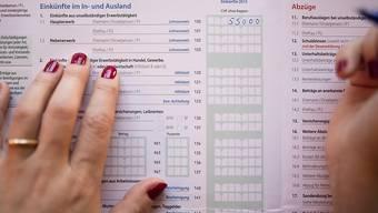 Die meisten tun es noch von Hand: Eine Frau füllt die jährliche Steuererklärung aus. (Symbolbild)
