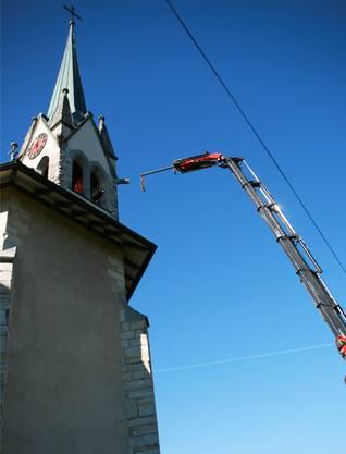 Ein Kran hievt Teile des Glockenstuhls vom Turm.