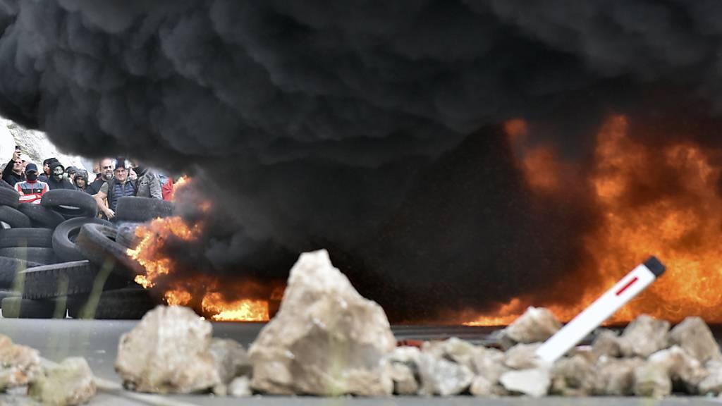 Rauch steigt von brennenden Reifen auf, die Demonstranten bei einer der Blockaden in Brand gesetzt haben. Foto: Risto Bozovic/AP/dpa