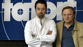 Die Schauspieler Axel Prahl, rechts, und Jan Josef Liefers, links, posieren vor einem Tatort-Logo. (Archivbild 2002).
