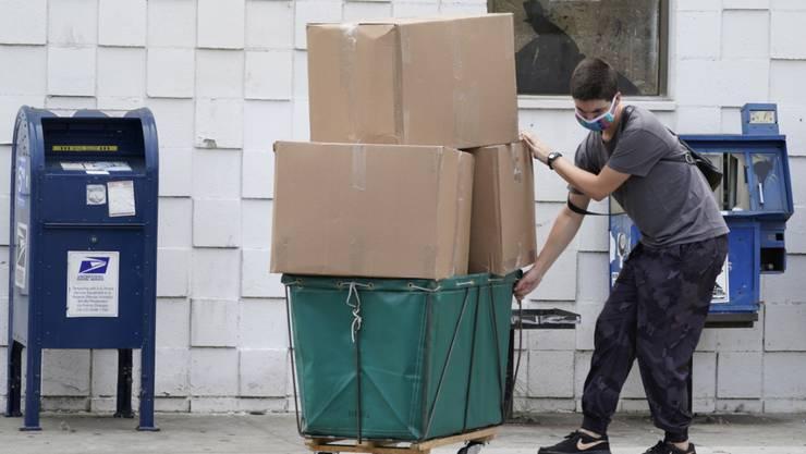 Ein Mann transportiert große Paketboxen. Foto: Damian Dovarganes/AP/dpa