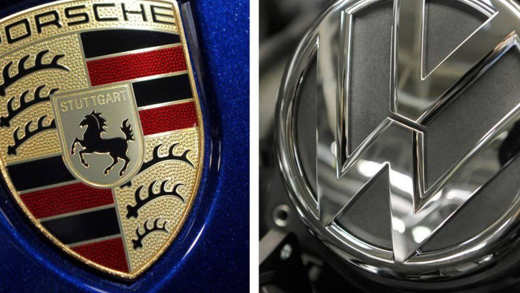 Porsche-Logo auf der Motorhaube eines Cayenne neben einem VW-Logo. (Symbolbild)