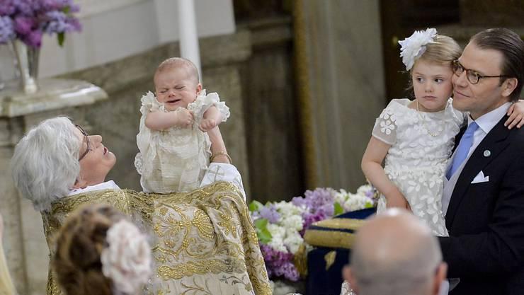 Prinz Oscar bei der Taufe, beobachtet von seiner Schwester Estelle und Vater Prinz Daniel