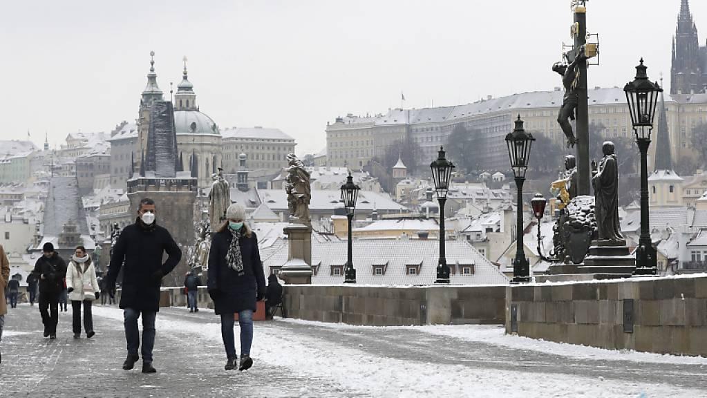 Menschen überqueren die mittelalterliche Karlsbrücke nach dem ersten Schneefall in Prag am ersten Tag der Lockerungen der Corona-Maßnahmen in Tschechien nach einem Lockdown. Am Donnerstag durften alle Geschäfte, Einkaufszentren, Restaurants, Bars und Hotels wieder öffnen. Foto: Petr David Josek/AP/dpa