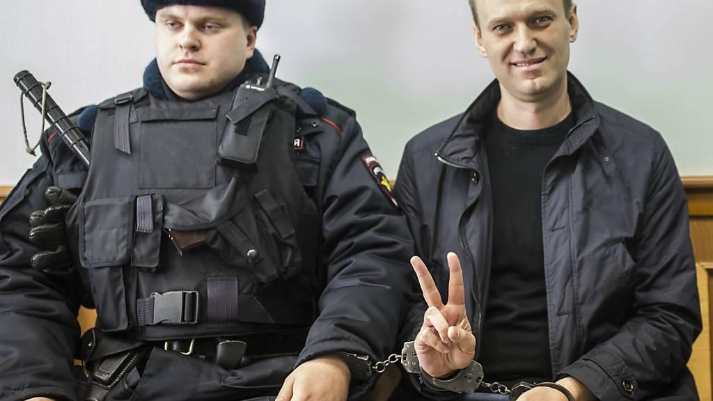 ARCHIV - Alexej Nawalny (r) zeigt ein Victory-Zeichen, während er neben einem Sicherheitsbeamten im Gericht sitzt. . Foto: Evgeny Feldman/AP/dpa