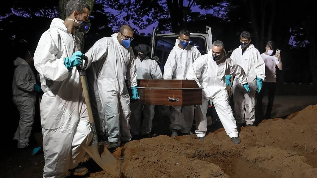 dpatopbilder - Mitarbeiter des Friedhofs Vila Formosa, dem größten in Lateinamerika, tragen einen Sarg, um eine an Covid-19 verstorbene Person zu beerdigen. Foto: Lincon Zarbietti/dpa