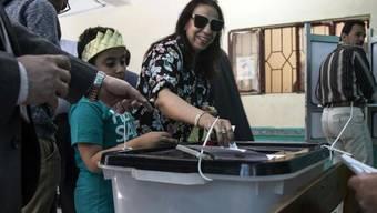 Eine Frau wirft ihren Stimmzettel in die Urne eines Abstimmungslokals in Kairo - die Ägypter befinden in einem Referendum über mehr Machtbefugnisse für ihren Präsidenten.