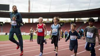 Der Nationalrat will bei Jugend und Sport nicht sparen. Im Bild: Leichtathlet Kariem Hussein trainiert mit Kindern im Stadion Letzigrund in Zürich (Archiv)