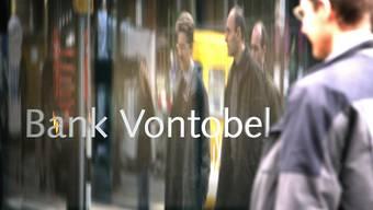 Passanten spiegeln sich in einem Schriftzug vor dem Hauptsitz der Bank Vontobel (Archivbild).