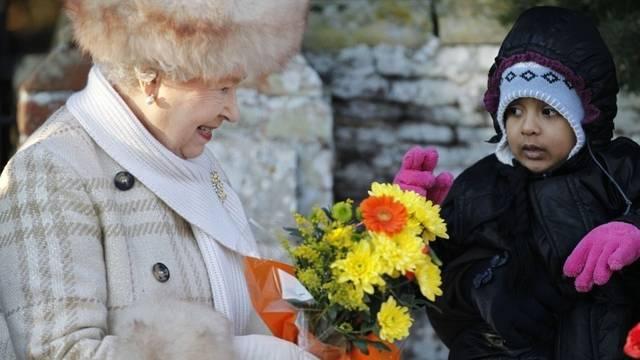Ein Kind überreicht der Königin nach dem Gottesdienst Blumen