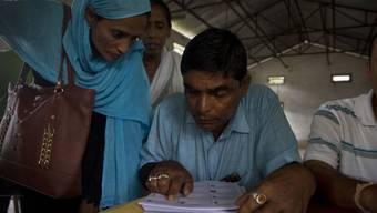 Dorfbewohner von Barburi im indischen Bundesstaat Assam kontrollieren, ob ihre Namen ins Nationale Bürgerregister aufgenommen worden sind.