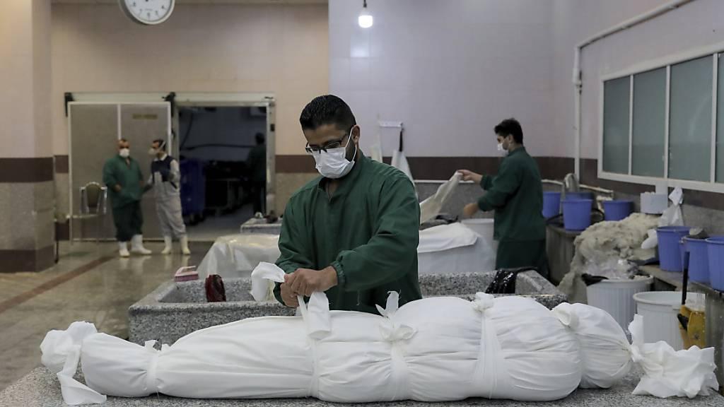 dpatopbilder - Ein Mitarbeiter bereitet in einem Leichenschauhaus in Teheran den Leichnam eines Mannes vor, der an den Folgen einer Corona-Infektion gestorben ist. Foto: Ebrahim Noroozi/AP/dpa