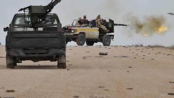 Rebellen feuern von ihren Geländewagen Schüsse ab