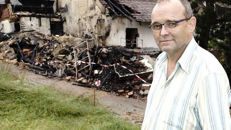 Pechvogel Hans Wüthrich steht vor den abgebrannten Gebäudeteilen seines Hofs in Reigoldswil.