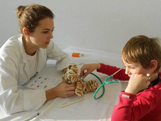 Ein Kindergärtler hört den Herzschlag seines Plüschtiers ab