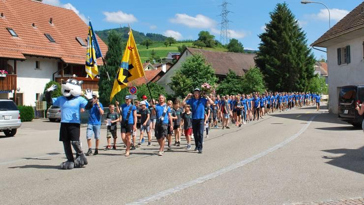"""Der traditionelle Einmarsch in Wölflinswil mit dem Maskottchen """"Lobo"""" an der Spitze"""