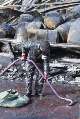 In Schutzanzuegen und mit Schutzmaske werden am 10. November 1986 bei den Aufräumarbeiten nach der Brandkatastrophe vom 1. November 1986 in Schweizerhalle nahe Basel ausgebrannte Fässer untersucht.