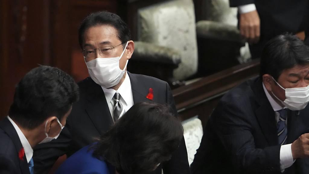 Japans Premierminister Fumio Kishida (M) und andere Abgeordnete sprechen nach der Auflösung des Unterhauses während einer außerordentlichen Sitzung des Parlaments. Foto: Eugene Hoshiko/AP/dpa