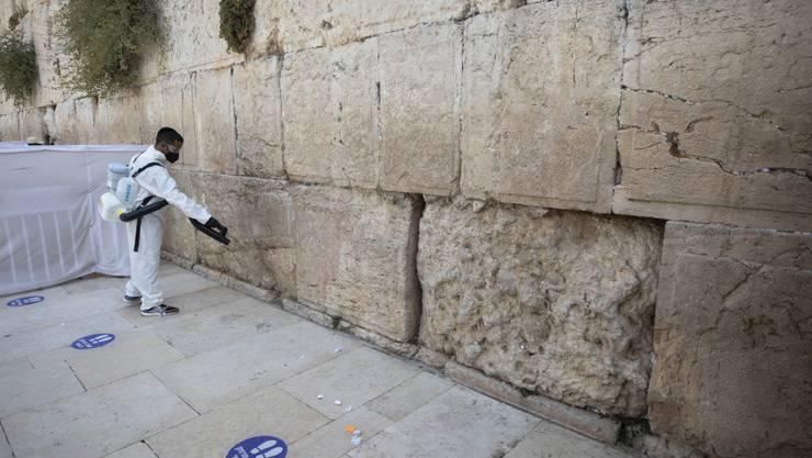 dpatopbilder - Ein Arbeiter verteilt Desinfektionsmittel als Vorsichtsmaßnahme gegen das Coronavirus an der Westmauer, der heiligsten Stätte, an der Juden in Jerusalem beten können. Foto: Sebastian Scheiner/AP/dpa