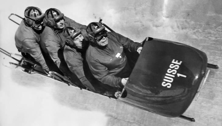 Das Bobteam Schweiz I mit dem Piloten Franz Kapus und seinen Hinterleuten Robert Alt, Gottfried Diener und Heinrich Angst, von vorne nach hinten, auf dem Weg zu ihrer Goldmedaille im Viererbob, aufgenommen an den olympischen Winterspielen in Cortina d'Ampezzo am 4. Februar 1956.