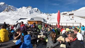 Schneesportler geniessen herrliches Wetter auf der Sonnenterrasse eines Bergrestaurants im Skigebiet Parsenn in Davos.